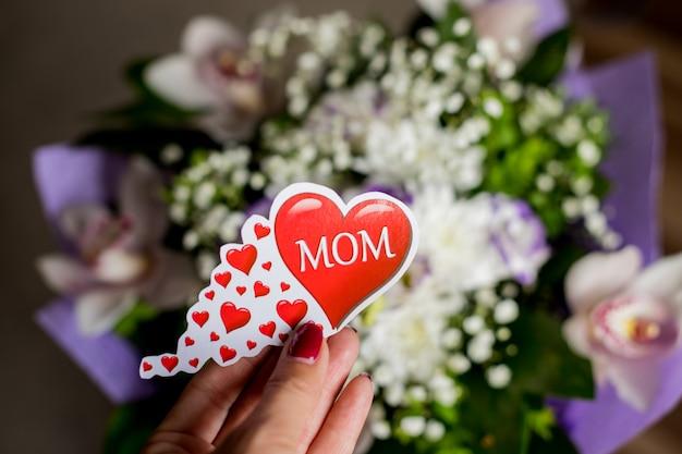 蘭、トルコギキョウ、カスミソウの花束。女性の手は、テキストのお母さんと大きな赤いハートを保持しています。母の日