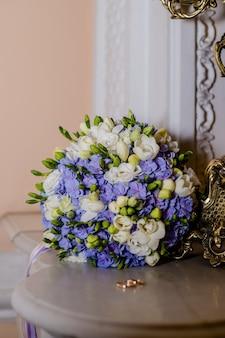Обручальные кольца и красивый букет как свадебные аксессуары. два золотых кольца и свадебные цветы.