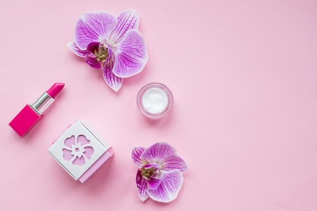 女性の香水のボトルと繊細な蘭の花