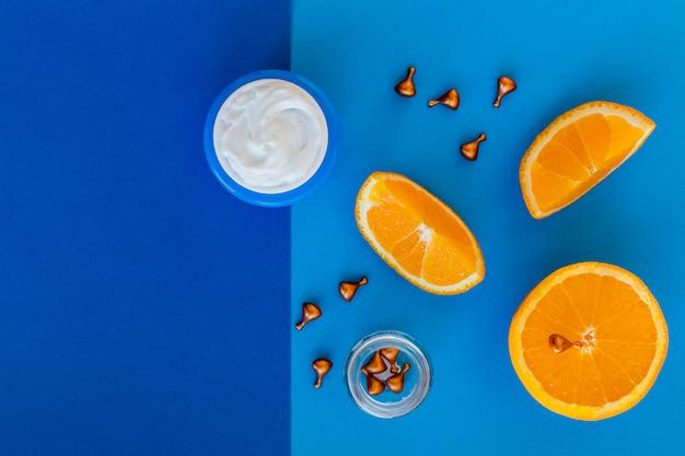 Витамин с, натуральная антивозрастная косметическая сыворотка и шприц с кусочками апельсиновых фруктов.