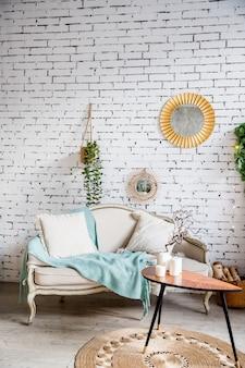 ベージュのソファ、ミントの毛布の上にベージュと質感の枕。キャンドルと小さなテーブル。ソファ、枕、エレガントなパーソナルアクセサリー、レンガの壁の植物のあるリビングルームのスタイリッシュなインテリア。