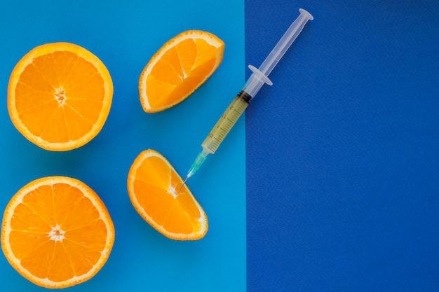 Витамин с, шприц на свежих сочных апельсиновых фруктовых горках. концептуальные изображения минералов, витаминов, медицинских добавок и здоровья. копирование пространства. концепция генетической модификации.