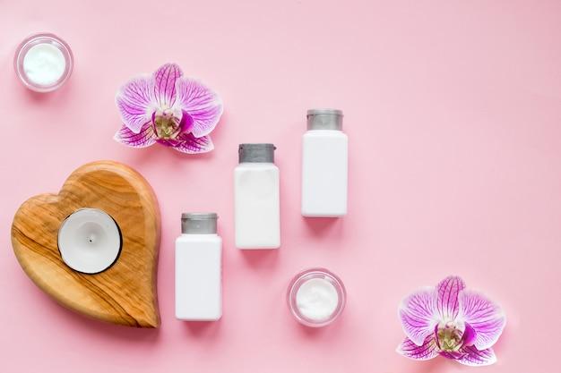 スパ美容製品。ココナッツオイル、クリーム、美容液、香水、キャンドル。美容ブログのコンセプト。スパの手順属性、顔とボディクリーム、蘭の花。レチノール保湿アンチエイジング