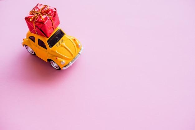 パステルの壁に分離された屋根の上のギフトボックスを提供する黄色のビンテージレトロなおもちゃの車を単に設計します。クリスマス、誕生日、お祝いプレゼント。配送、ショッピング、販売コンセプト。