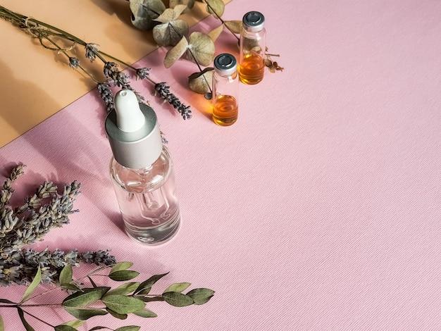 パステルの壁にハーブオイルとラベンダーの花。ラベンダーとエッセンシャルオイルのボトル。自家製スパ用のラベンダーとオレンジ、レモンの自然化粧品