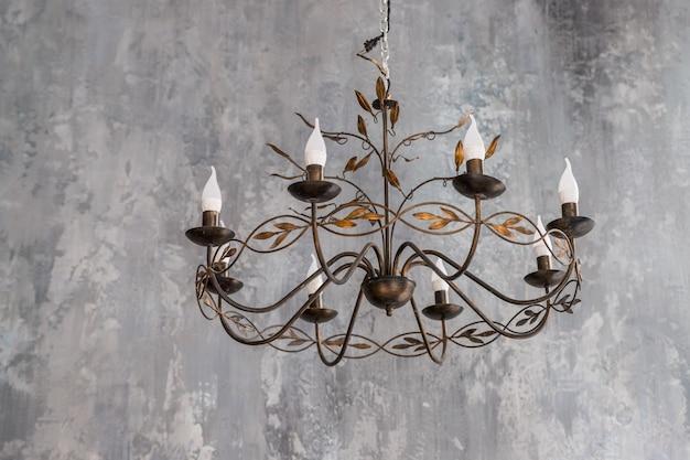 天井に掛かっている豪華な黒い金属製のシャンデリア。現代的なシャンデリア、天井や壁に取り付けるように設計された装飾用の照明器具。ホームインテリア