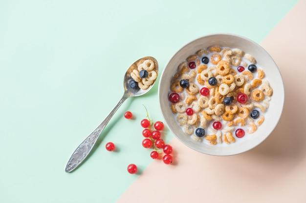 ブルーベリー、赤スグリ、スプーンのオート麦シリアルのボウル。ベリーとミルクのオートリングシリアル。健康的な朝食、健康的な食事の概念。フラット横たわっていた、ミニマリズム、トップビュー。テキストのための場所。