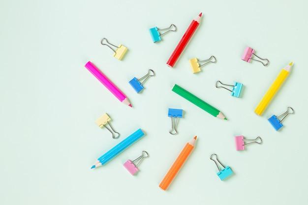 Школьное оборудование. разнообразие школьных принадлежностей. пастельный фон с красочными карандашом и скрепкой. концепция подготовки к школе. шаблон.