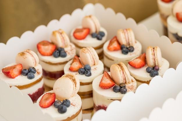 新鮮なベリーで飾られたお菓子。ベリーとバニラクリームの小さなケーキ。マカロンは甘いメレンゲベースの菓子です。