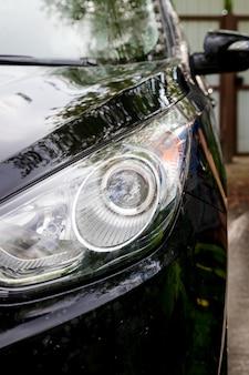 屋外の洗車。穏やかな洗車。石鹸と水で覆われた現代の車。自動車、自動洗浄泡水、自動詳細またはバレッティングコンセプト。セレクティブフォーカス。