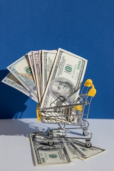 Корзина и доллар на синей стене, интернет-магазины. креативная рекламная композиция для интернет-магазина распродажи и продуктовой корзины.