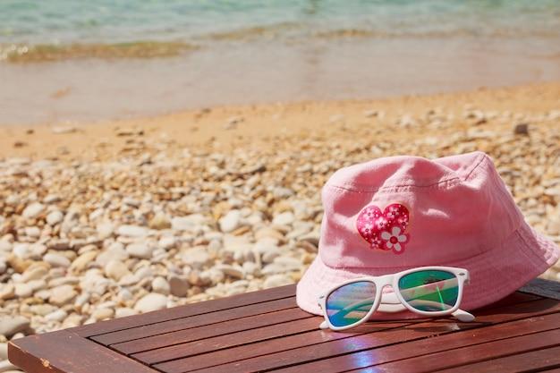 休日のサングラスと白い帽子のビーチで日焼け止めオブジェクト