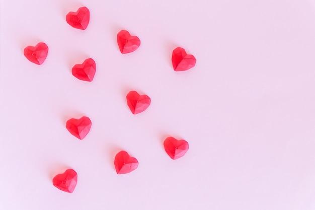 Розовый фон ко дню святого валентина. декоративные красные сердечки