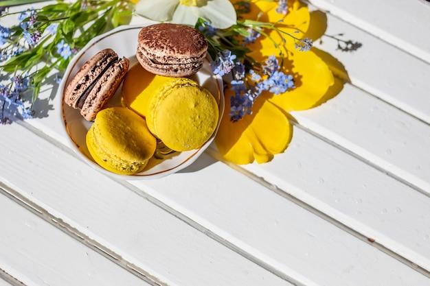 フランスのマカロン菓子と柔らかい花が木製の背景に花します。