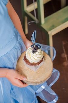 ベリーとおいしいカップケーキを保持している女の子。ブルーベリークリームとベリーとバニラのカップケーキ。セレクティブフォーカス。豪華なケータリングのコンセプト。チーズクリームとカップケーキ
