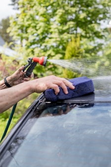 Мужская рука чистит черный автомобиль губкой и шлангом.