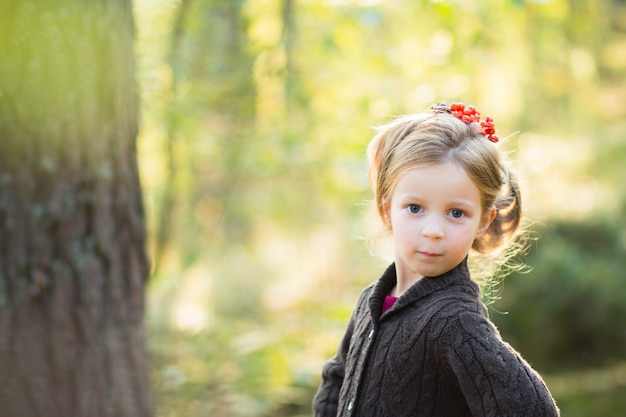 ナナカマドの果実の美しい髪型と自然の中でかわいい女の子。