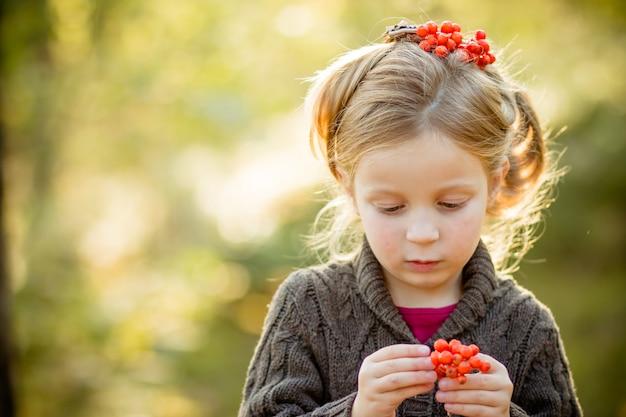 ナナカマドの果実を保持しているセーター、ニット帽子、スカーフを身に着けているかわいい幼児の女の子。