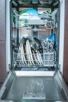 清潔なガラスと皿を備えたオープン食器洗い機。食器洗い機できれいな皿とカトラリー。