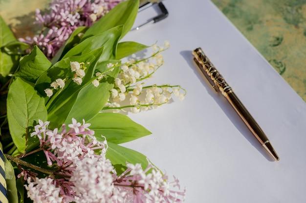ゴールデンペンと木製のテーブルの上の空白の紙