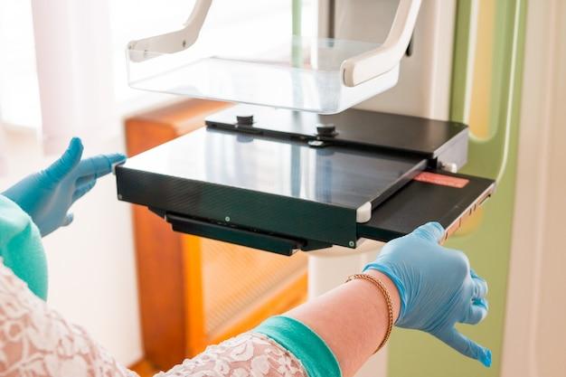 Симпатичная молодая девушка на осмотре груди с помощью маммографического рентгеновского аппарата