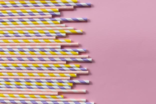 ピンク色の背景に色とりどりの紙ストロー
