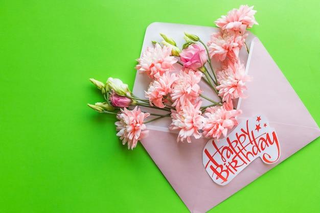 美しいフラワーアレンジメント。封筒とピンクの菊。フラット横たわっていた、上面図。お誕生日おめでとうございます