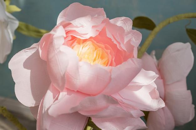 紙から手作りのピンクの花がたくさん。イベントや休日のための内壁と床の上の美しい花の和紙花