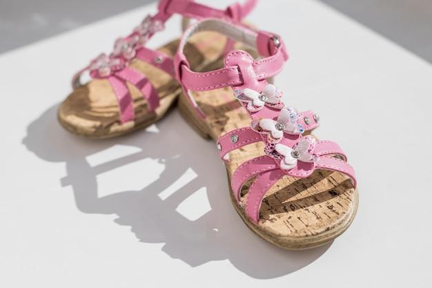 ピンクのサンダルは、白い背景で隔離。女の子用の靴、スリッパ、赤ちゃん用のビーチファッション。