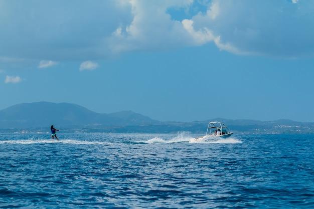 Женщина скользит на водных лыжах по волнам на море