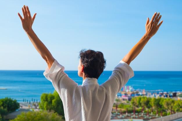 夏の朝にバルコニーで両手を広げて女性の後ろからの眺め。