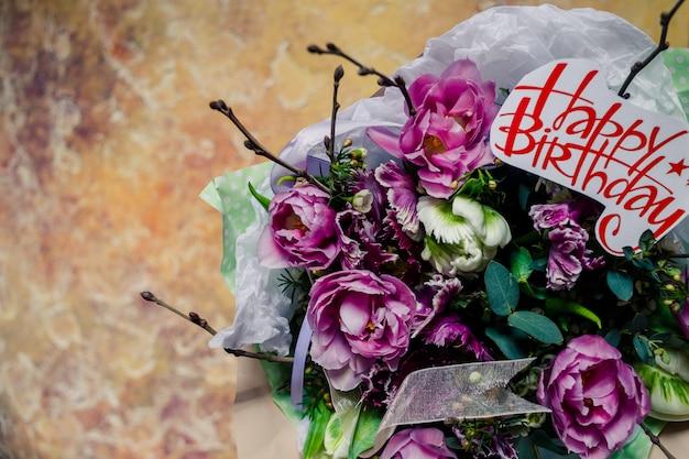 ピンクの牡丹、チューリップ、お誕生日おめでとうございますプレゼントの花束。ピンクの花、休日のための花。