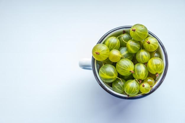 白いコップジューシーな新鮮で熟したグリーングーズベリー、夏のデトックス食品のコンセプトでいっぱい。スペースをコピーします。