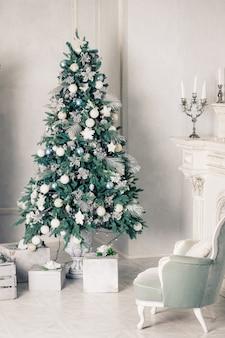 Роскошный интерьер гостиной с диваном, украшенным шикарной елкой, подарками, пледом и подушками.