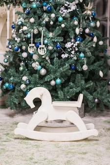 子供用おもちゃの揺り木馬は白いクリスマスツリーです。近くには贈り物や休日の染色があります。花輪と青いボケ