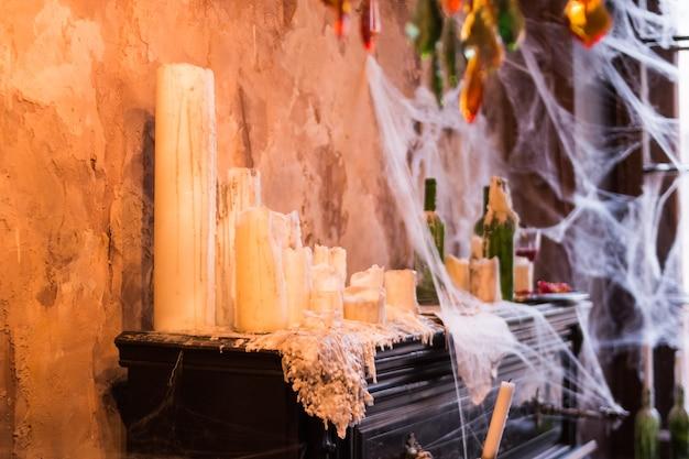 ピアノの上に立っている多くのキャンドル。不気味なクモの巣お化け屋敷の設定でキャンドルと燭台の瓶で覆われています。ハロウィーンパーティーのためのインテリアや装飾品。お化け屋敷の静物画。