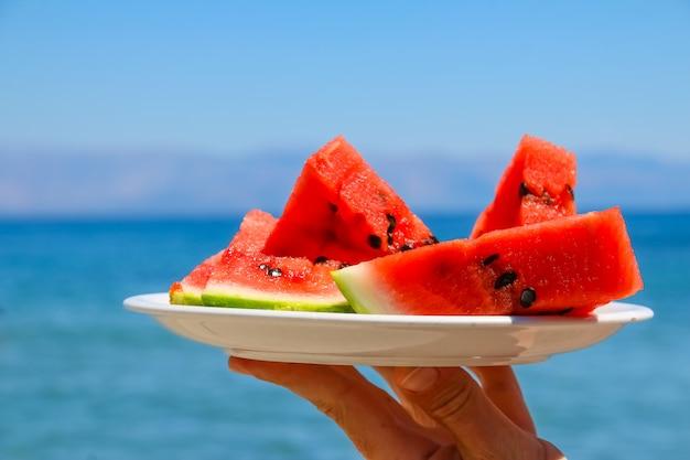青い海の背景に皿の上のスイカのスライス。ビーチで新鮮な果物。