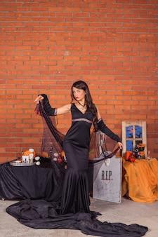 ハロウィーンの吸血鬼の衣装を持つ女性。ハロウィーンのテーマのインテリアの家の装飾