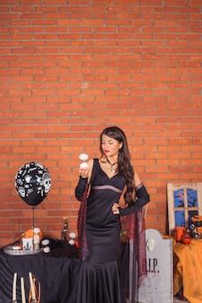 黒魔女のハロウィーンの衣装で美しいセクシーな女性の肖像画。幸せなハロウィーンのコンセプト。トリック・オア・トリート。面白い秋のパーティー、垂直写真
