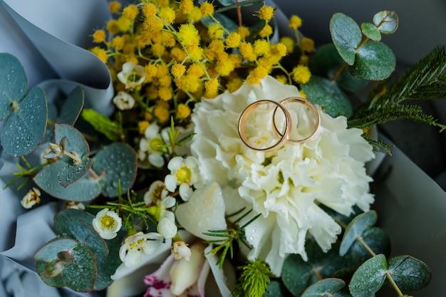 Обручальные кольца лежат и красивый букет в качестве свадебных аксессуаров. два золотых кольца и свадебные цветы.
