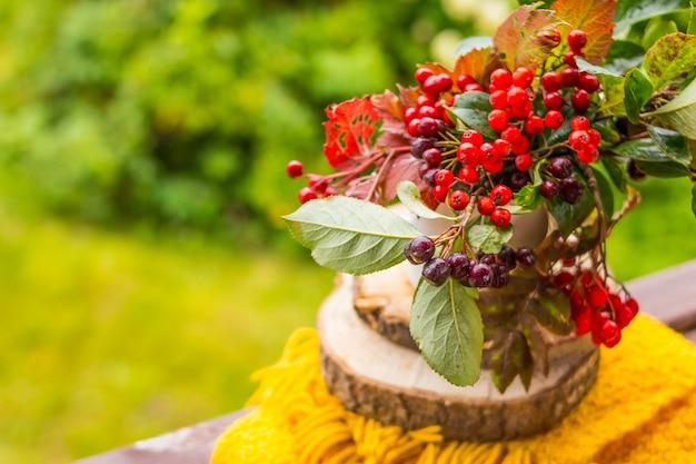 花瓶にガマズミ属の木とチョークベリーの果実