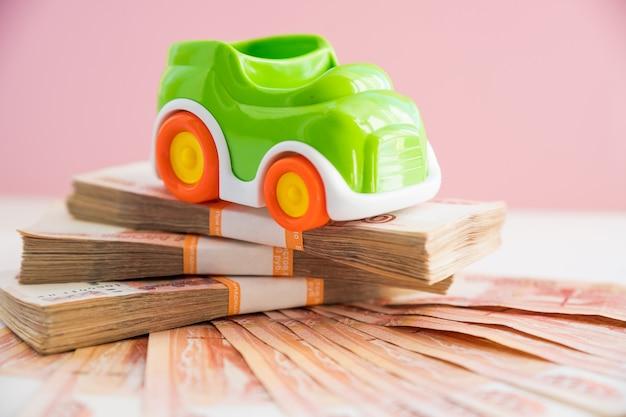 Модель игрушечной машины и пачки купюр