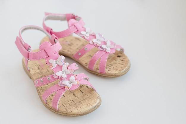 分離された蝶とピンクの赤ちゃん女の子サンダル。夏用のトレンディで快適なシューズ。