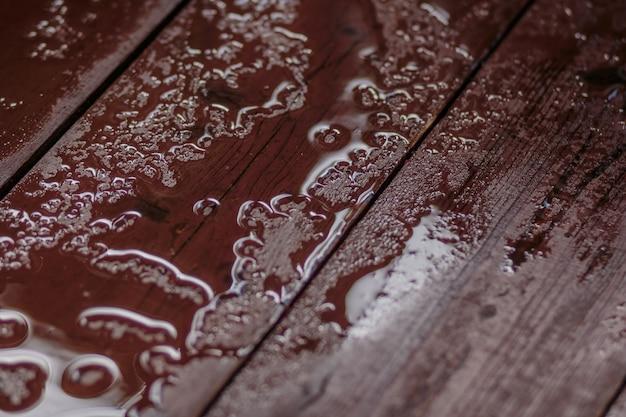 雨の後、木製のテーブルに雨の滴。水滴の空の木製テーブル。