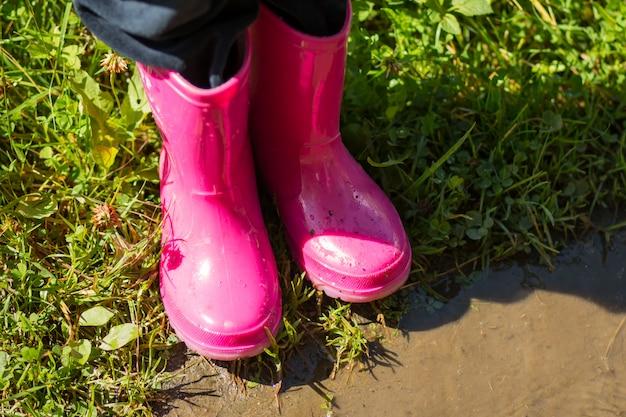 水たまりに飛び込む赤ピンクの長靴を着ている子。子供明るい赤ゴム長靴、ガーデニング、ブーツ。雨の日のファッション。庭の雨のラバーシューズ。雨の日のブーツ。秋の子供ブーツのコンセプト。