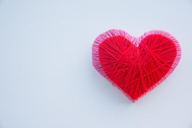 カラフルな糸玉が分離されました。愛のシンボルのような赤とピンクのハート。趣味