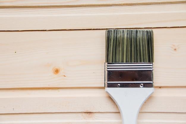 木製のハンドルを持つ大きなペイントブラシ。木製の背景に分離されたペイントブラシ。上面図
