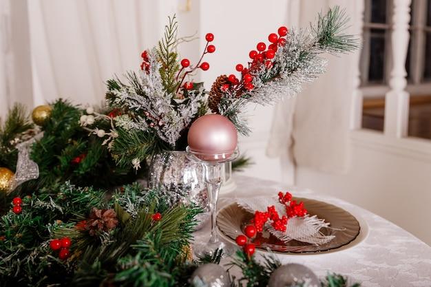 冬の装飾と白いキャンドルの中でお祝いテーブルの設定。トップビュー、フラットレイアウト。クリスマスまたは感謝祭の家族の夕食の概念。