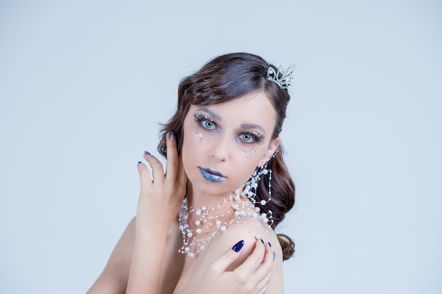 Молодая женщина в творческий образ с серебряной художественного макияжа. красивое женское лицо.