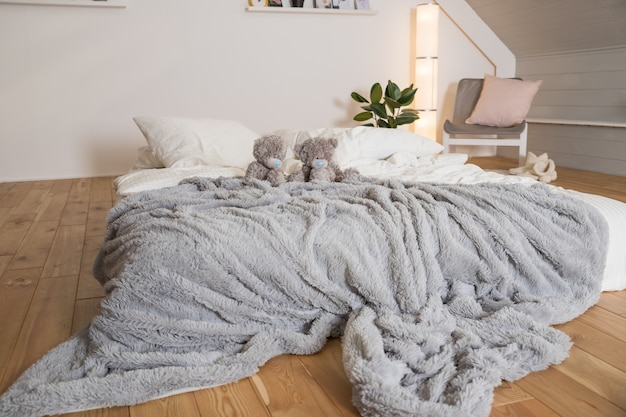 Скандинавская спальня с торшером, растением, серой стеной, белой мебелью, плюшевыми мишками. стильный, яркий скандинавский декор. концепция древесины и природы в интерьере комнаты.